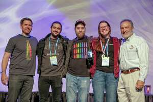Great American Beer Festival founder Charlie Papazian (R) poses with Barebottle Brewing Company staffers at the Great American Beer festival on Saturday, October 5, 2019.