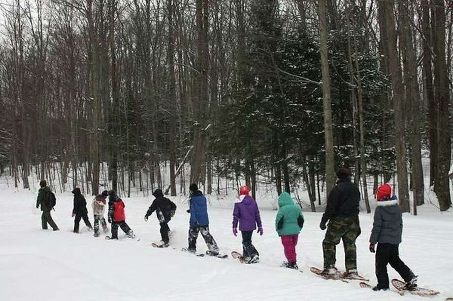 Students hike into the woods through fresh snow while on a Snowshoe Experience field trip. (Courtesy photo/National Park Service)