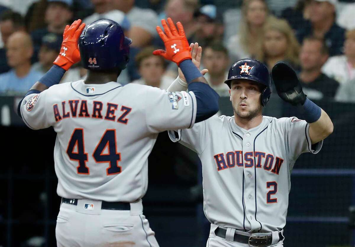 Houston Astros designated hitter Yordan Alvarez (44) crosses the plate behind Alex Bregman (2) after they scored on a single by Yuli Gurriel during the sixth inning of Game 3 of the American League Division Series against the Tampa Bay Rays at Tropicana Field on Monday, Oct. 7, 2019, in St. Petersburg, Fla.