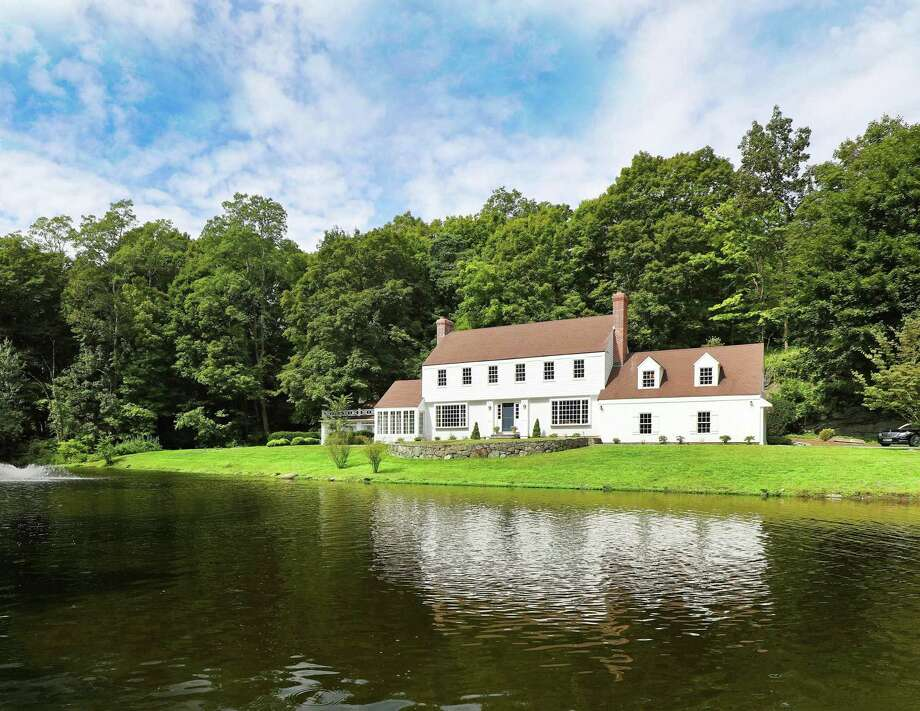 The classic New England colonial house at 239 Olmstead Hill Road sits on a 1.86-acre along a natural pond.