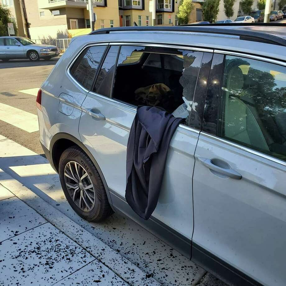 The black tablecloth Famellos used to shroud her valuable objects is seen dangling out of the smashed rear passenger window of her Volkswagen. Photo: Anzula Luxury Fibers