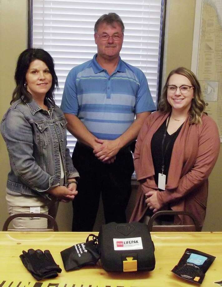 From left, Shelly Grifka, Huron County Sheriff Kelly J. Hanson and Katie Alexander pose with an AED device and puncture resistant gloves that were purchased through grants. (Submitted Photo)