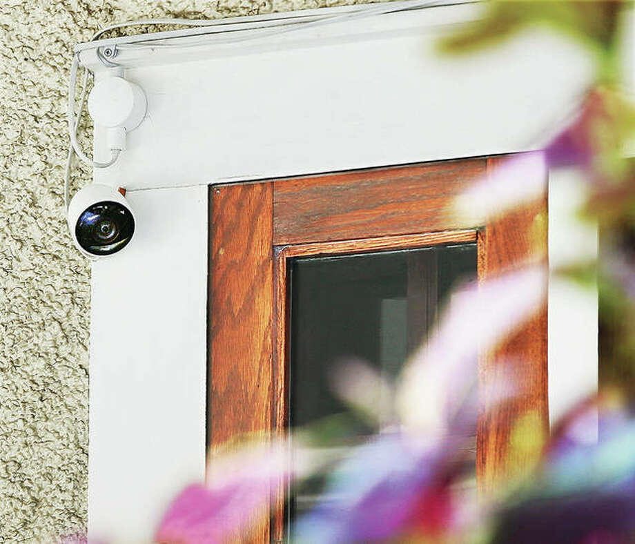 A home surveillance camera keeps a close eye on the front porch of a house Monday on State Street in Alton. Police are asking people with exterior home cameras to contact them so that their names and addresses can be added to a list to help solve neighborhood crimes around the city.