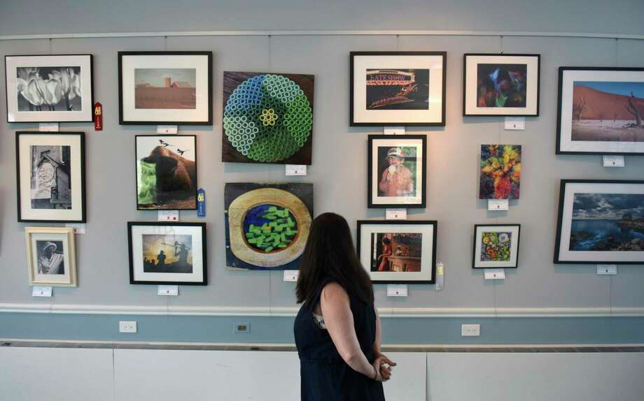 GBC Board President Meg McAuley Kaicher looks at photographs displayed for the Art Society of Old Greenwich 2019 Fall Exhibition at the Greenwich Botanical Center in Cos Cob. The work will be displayed until Monday. Photo: Tyler Sizemore / Hearst Connecticut Media / Greenwich Time