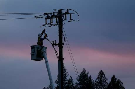 FILE - In this Nov. 26, 2018, file photo, a Pacific Gas & Electric lineman works to repair a power line in fire-ravaged Paradise, Calif. PG&E says it could cut off power to a large swath of Northern California later this week to prevent its equipment from starting wildfires during hot, windy weather. The utility says power could be shut off in 30 counties in central and Northern California starting Wednesday, Oct. 9, when hot weather and strong winds are forecast, and through Thursday. (AP Photo/Rich Pedroncelli, File)