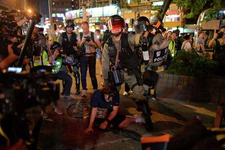 Police detain a protester (C) on a street near Mong Kok police station in Hong Kong on Oct. 7, 2019. Hong Kong protesters arrested for defying a new face mask ban appeared in court on Oct. 7 following a violent weekend of unrest which saw bloody clashes with police and widespread vandalism that crippled the city's train network.