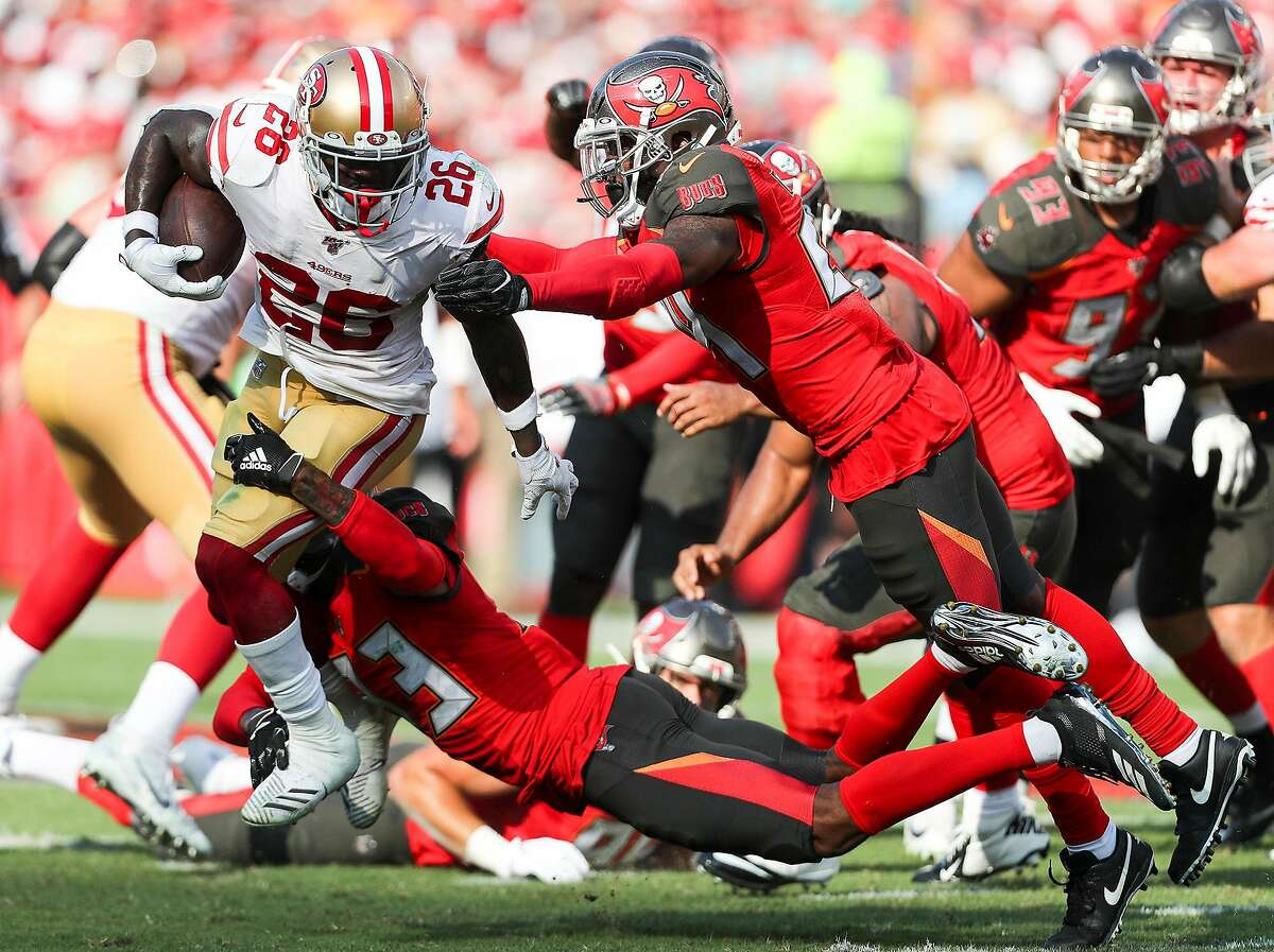 San Francisco 49ers running back Tevin Coleman (26) gets tackled by Tampa Bay Buccaneers cornerback Carlton Davis (33) and safety Darian Stewart (24) during the second quarter on Sunday, Sept. 8, 2019 at Raymond James Stadium in Tampa, Fla. (Monica Herndon/Tampa Bay Times/TNS)