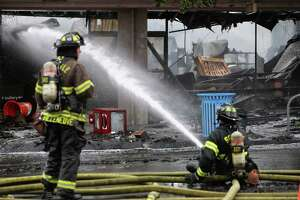 Firefighters work to extinguish a 3-alarm fire that broke out in the 2300 block of NW Market Street and destoryed several businesses, including Kitchen N' Things, La Isla Restaurant and Supercuts.
