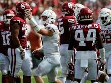 Texas Longhorns quarterback Sam Ehlinger (center) signals after a first down run during the second half of an NCAA college football game against the Oklahoma Sooners, Saturday, Oct. 6, 2018, in Dallas, Texas. (AP Photo/Roger Steinman)