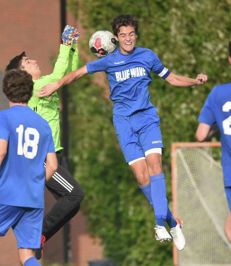 Darien's Will Henry Harmon goes high for a shot in front of Stamford goalkeeper Adrian Torres on Monday. Photo: Dave Stewart / Hearst Connecticut Media / Hearst Connecticut Media