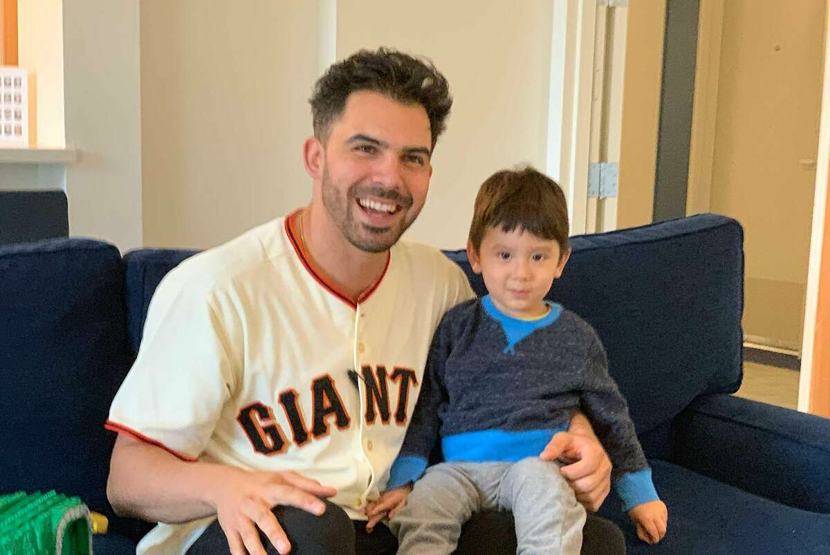 Giants minor-league pitcher Tyler Cyr poses with a patient at Family House in San Francisco, during a visit to the nonprofit organization that houses families of children undergoing treatment for serious illnesses.