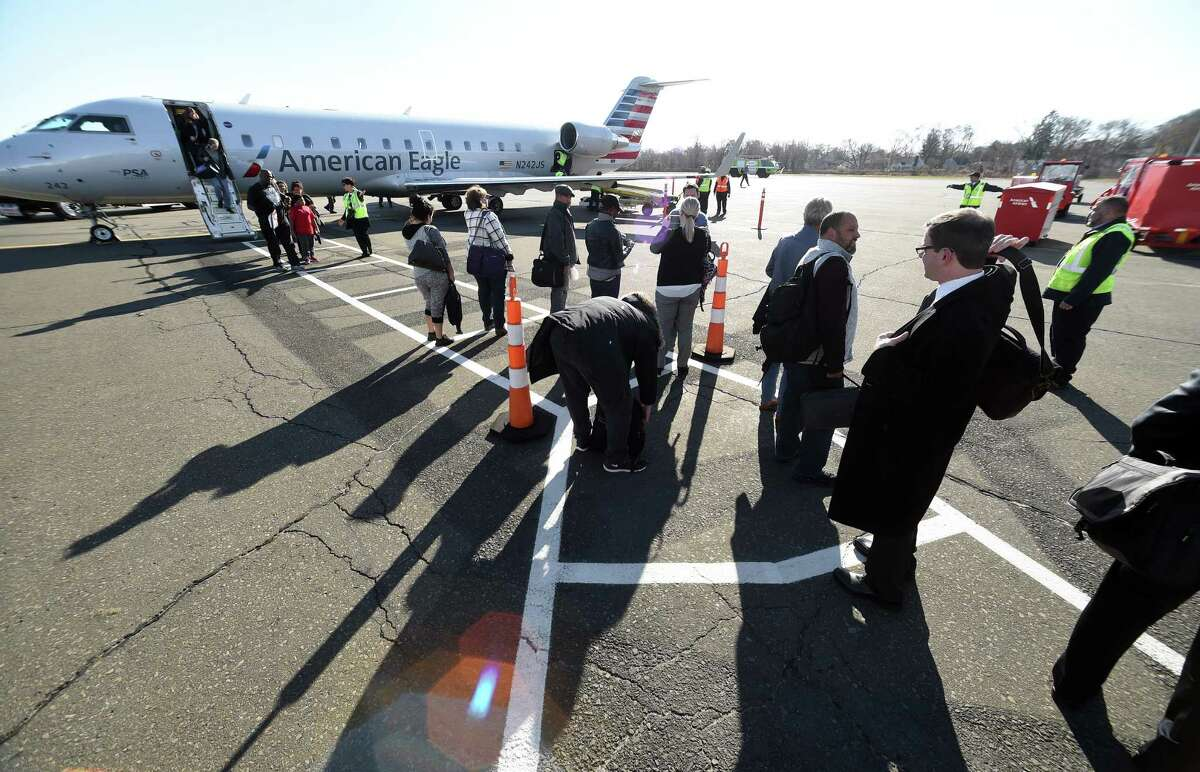 Passengers disembark the first American Eagle Canadair RJ 200 regional jet originating in Philadelphia and landing at Tweed New Haven Airport in New Haven on November 29, 2017.