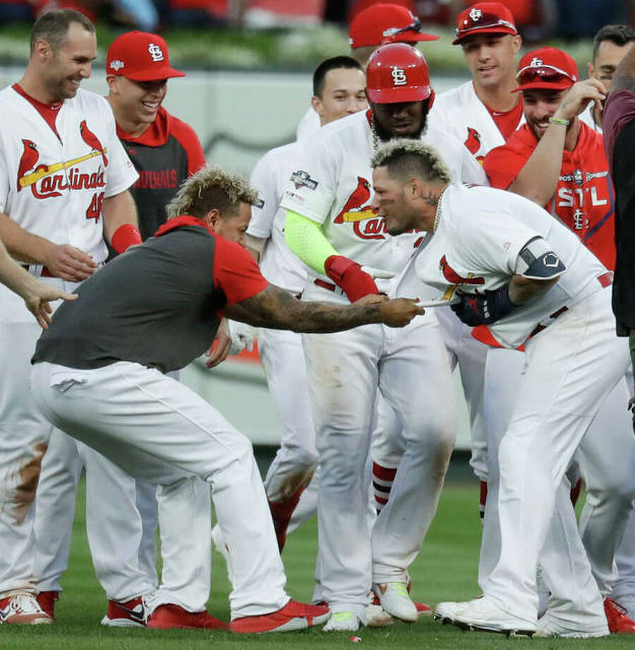 The Cardinals' Yadier Molina (right) celebrates with the team after his sacrifice fly drove in the winning run in the 10th inning to beat the Braves on Monday in St. Louis. Photo: Associated Press