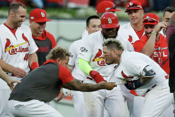 The Cardinals' Yadier Molina (right) celebrates with the team after his sacrifice fly drove in the winning run in the 10th inning to beat the Braves on Monday in St. Louis.