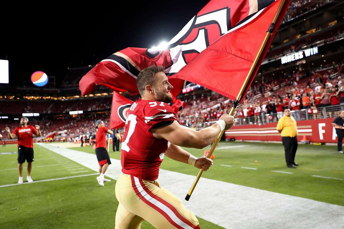 San Francisco 49ers' Nick Bosa celebrates with team flag after 31-3 win over Cleveland Browns during NFL game at Levi's Stadium in Santa Clara, Calif., on Monday, October 7, 2019.