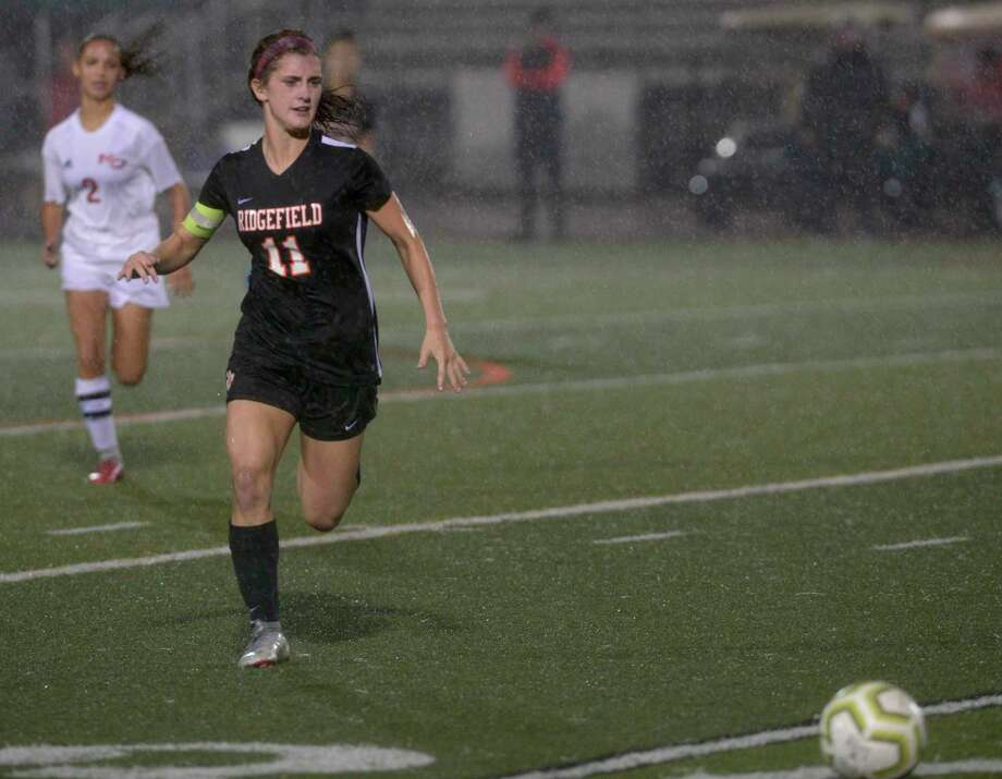 Ridgefield's Caitlin Slaminko (11) chases down the ball ahead of New Canaan's Sophie Potter (2) in the girls soccer game between New Canaan and Ridgefield high schools, Monday night, October 7, 2019, at Ridgefield High School, Ridgefield, Conn. Photo: , H John Voorhees III / Hearst Connecticut Media / , The News-Times