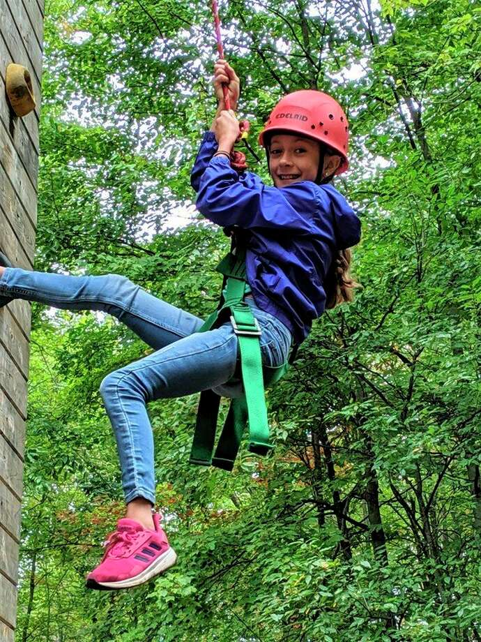 Blessed Sacrament fifth grader Payton Mathe is all smiles as she descends the 30-foot rock wall at Camp Timbers. Blessed Sacrament School fifth graders recently spent three days at camp. (Photoprovided)