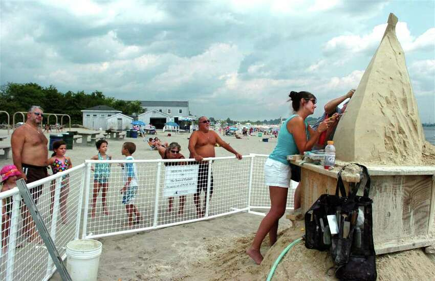 Beachgoers watch as Tracey Fitzpatrick and her husband Sean mold 10 tons of sand into a 12-foot by 10-foot sailboat Friday August 6, 2010 at Penfield Beach in Fairfield. The process began on Thursday and the craft will be completed by Saturday afternoon.