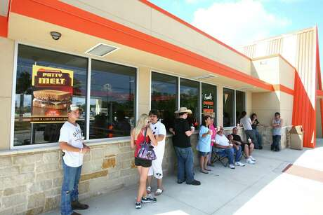 Whataburger customers, some of whom have camped out since Sunday night, wait in line to be one of the first 20 customers to receive free food for a year at the grand opening of a Whataburger restaurant in Willis on Monday.
