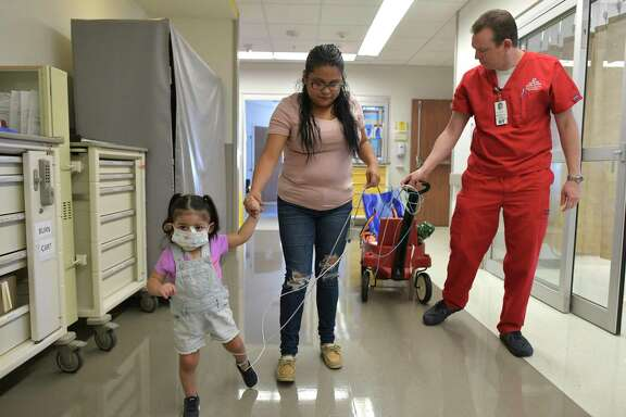 Addison Gonzalez, who was severely injured after she fell into a septic tank, walks with her mother, Lilian Garcia, and Casey Howard, director of the ECMO group at University Hospital, on Oct. 4, 2019. ECMO, or extracorporeal membrane oxygenation, supports the functions of a person's heart and lungs. It was used to save Addison's life.