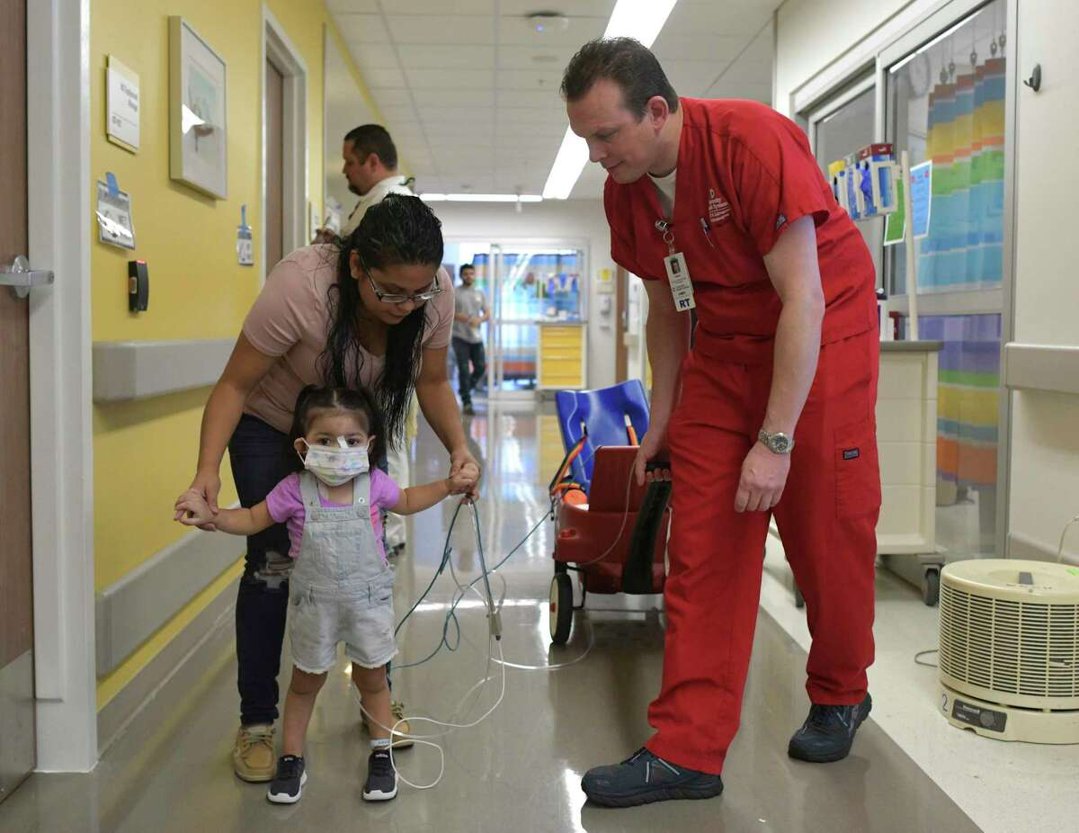 Addison Gonzalez is helped by her mother, Lilian Garcia, at University Hospital, where she is being treated after falling into a septic tank in Harlingen. Addison was exposed to the toxic gas hydrogen sulfide, prompting the use of an ECMO machine to support her heart and lungs. Casey Howard, director of the ECMO department at University Hospital, walks with Addison on Friday, Oct. 4, 2019.
