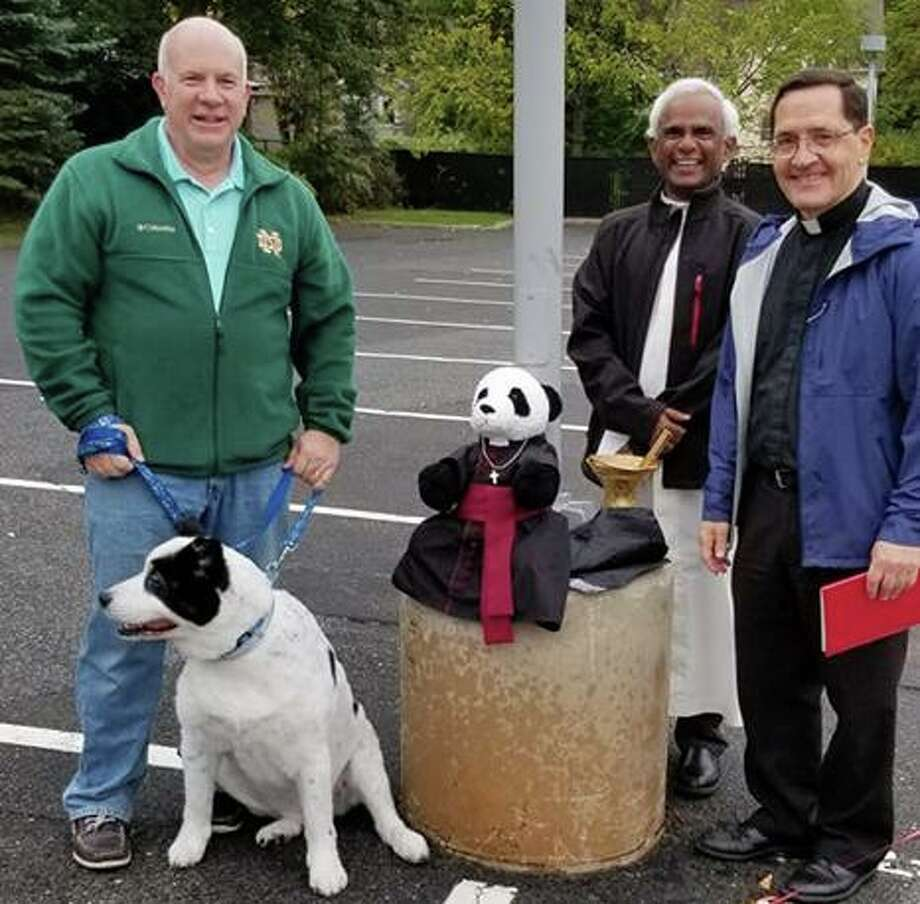 A St. Mary parishioner with his dog, left, stands with Monsignor Kevin Royal and Fr. Lourduraj at the church's Blessing of the Animals ceremony on Sunday, Oct. 6. Photo: Contributed Photo