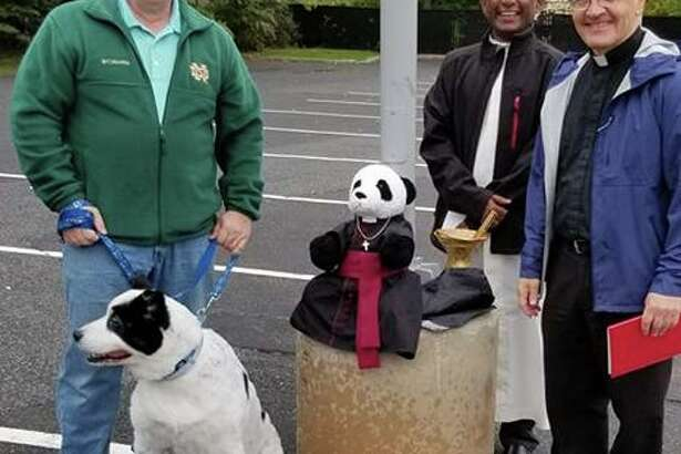 A St. Mary parishioner with his dog, left, stands with Monsignor Kevin Royal and Fr. Lourduraj at the church's Blessing of the Animals ceremony on Sunday, Oct. 6.