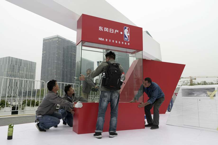 Workers dismantle signage Tuesday for an NBA fan event scheduled to be held Wednesday night at the Shanghai Oriental Sports Center in Shanghai, China. Chinese state broadcaster CCTV announced Tuesday it will no longer air two NBA preseason games set to be played in the country. Photo: AP Photo