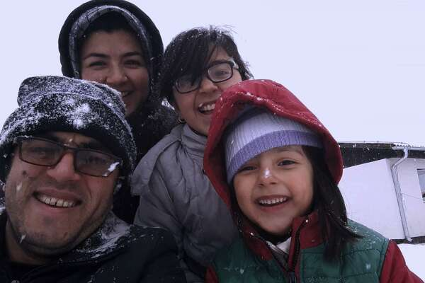"""Hassan Fazili, bottom left, and his wife, filmmaker Fatima Hussaini, top left, with their daughters, Nargis, top right, and Zahra in a scene from """"Midnight Traveler."""" (Oscilloscope Laboratories/TNS)"""