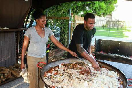 Chefs Dawn Burrell of Kulture and Chris Williams of Lucille's, stirring jambalaya at Indigo, during a garden party where boxes of fresh produce were given directly to the residents of the Trinity Gardens community.