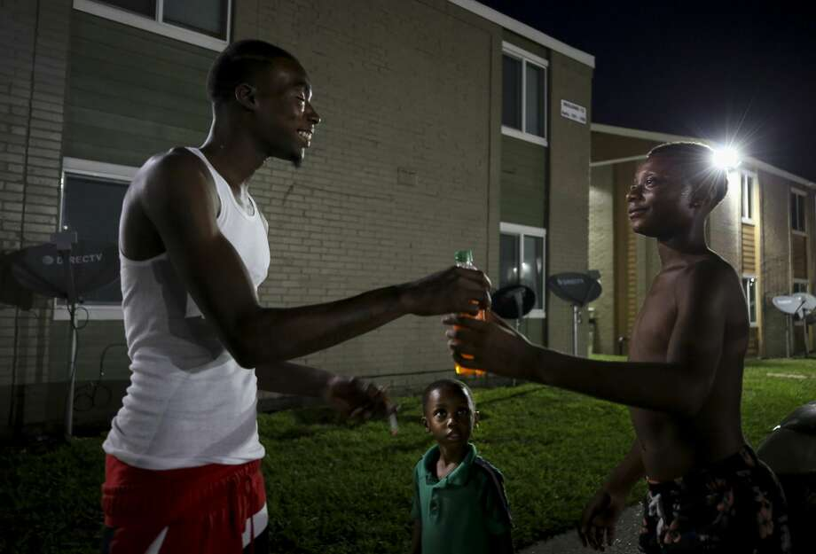 Sleepy, left, shares his bottle of Fanta with a teenager as Garden City residents hang out outside in Houston. Photo: Godofredo A. Vásquez/ Staff Photographer