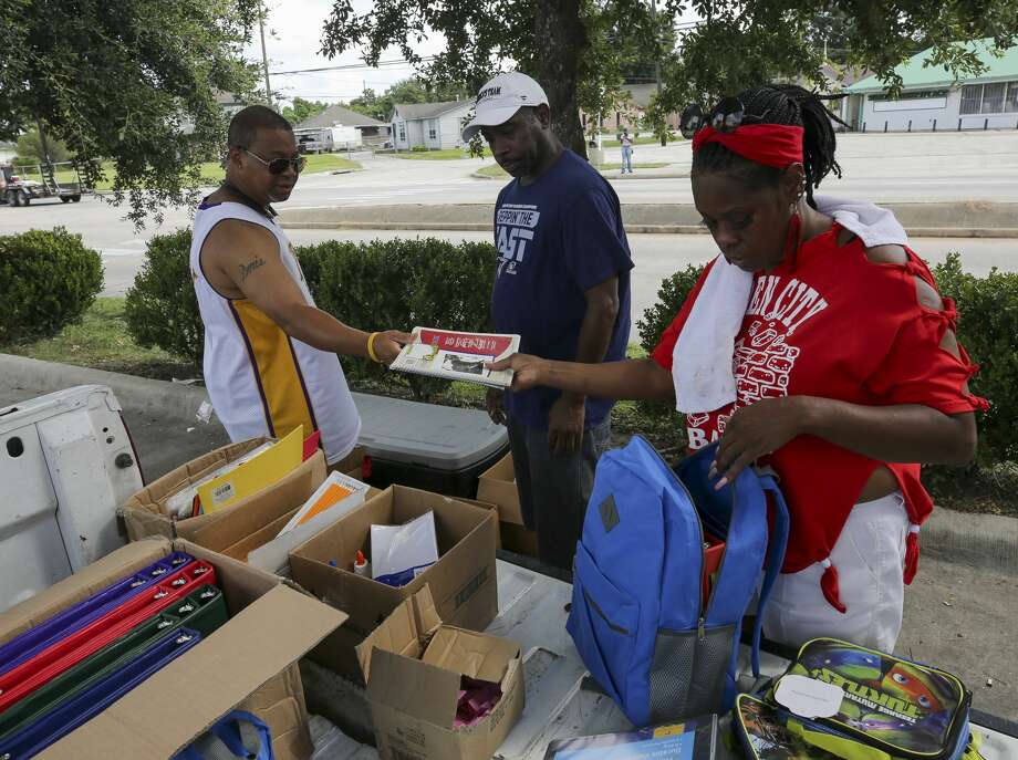 Darrin Turner, left to right, Dexter Minor, and Deidra Barrow fill backpacks with back-to-school supplies for children who live in the Garden City Apartments in Houston. Photo: Godofredo A. Vásquez/ Staff Photographer
