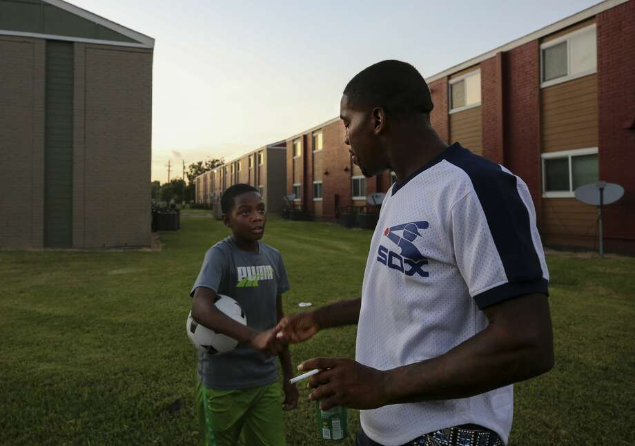 Dezmond Jackson, also known as Ceasar, right, chats with a young boy at the Garden City Apartments. Photo: Godofredo A. Vásquez/ Staff Photographer