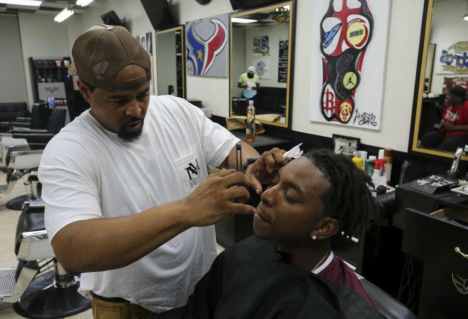 Corey Johnson, left, cleans up Travon Dow's edges inside his barber shop, Prime Time Barbershop. Photo: Godofredo A. Vásquez/ Staff Photographer