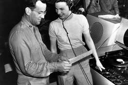 """Marjorie Ochs, the only female in the radio program """"Sustain the Wings,"""" goes over the script with bandleader Capt. Glenn Miller on June 16, 1943, at Yale University. The show was presented by the Army Air Force's Technical Training Command at Yale over a national radio hook-up."""
