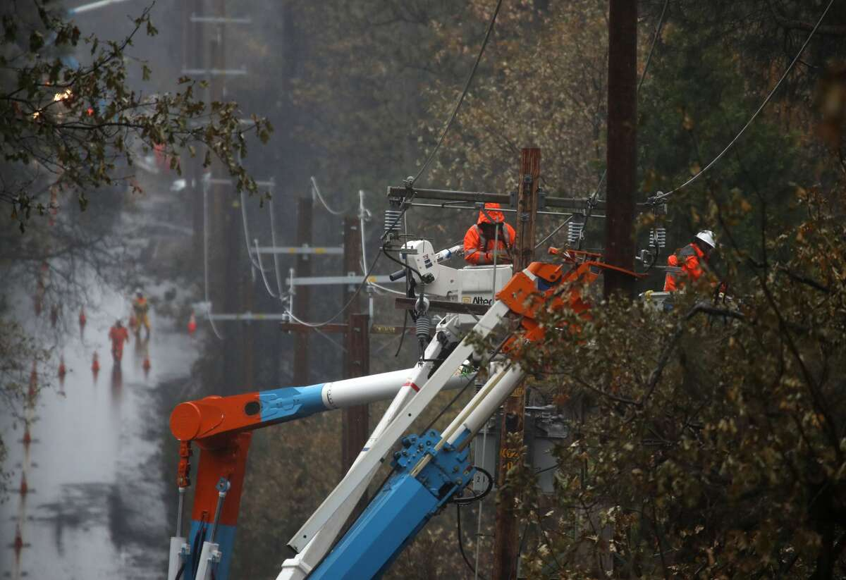 Pacific Gas and Electric (PG&E) crews repair power lines that were destroyed by the Camp Fire on November 21, 2018 in Paradise, California. Fueled by high winds and low humidity the Camp Fire ripped through the town of Paradise, charring over 150,000 acres and killing 85 people.