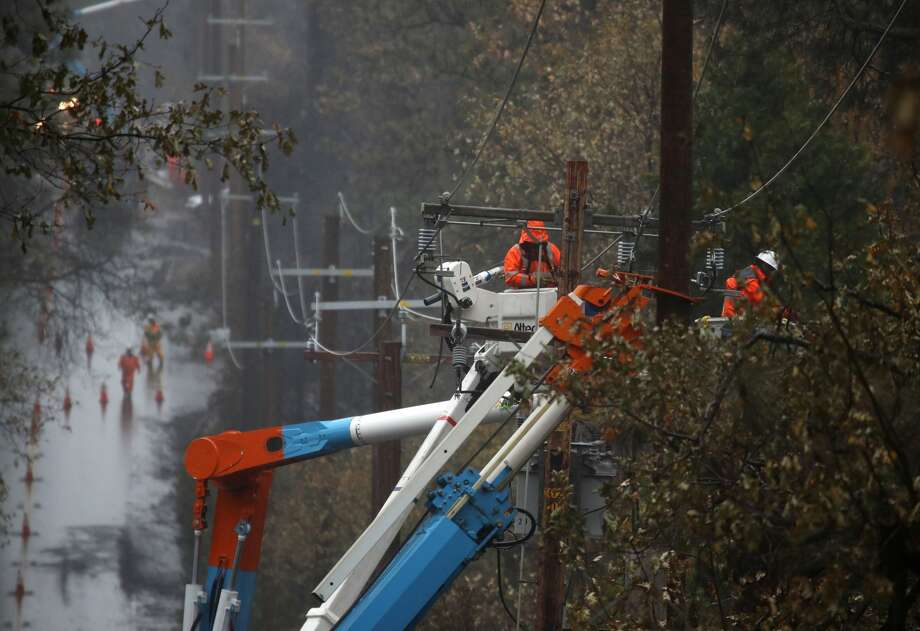 Pacific Gas and Electric (PG&E) crews repair power lines that were destroyed by the Camp Fire on November 21, 2018 in Paradise, California. Fueled by high winds and low humidity the Camp Fire ripped through the town of Paradise, charring over 150,000 acres and killing 85 people. Photo: Justin Sullivan/Getty Images