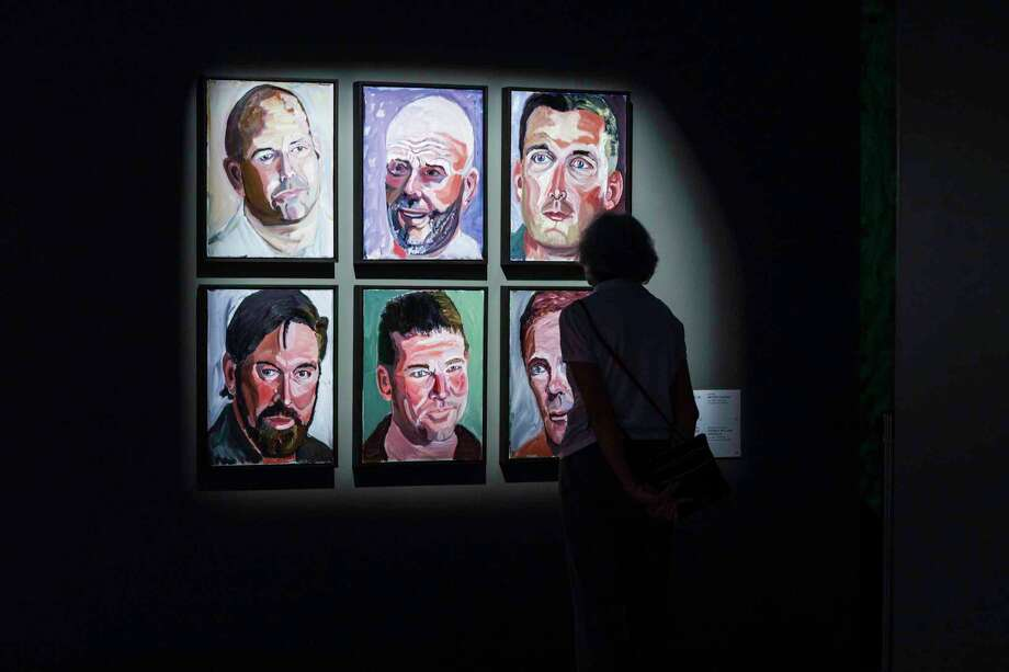 """A visitor views """"Six Portraits in Studio,"""" painted by George W. Bush and featured in """"Portraits of Courage"""" at the Kennedy Center in Washington, D.C. Photo: Jati Lindsay/The Kennedy Center / Jati Lindsay"""