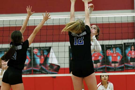 Crosby junior outside hitter Karsyn Shaver, right, works at the net against Friendswood's sophomore middle blocker Sarah Sitton (12) and sophomore outside hitter Kate Bueche, left, during their district matchup at Crosby High School on Sept. 27, 2019.