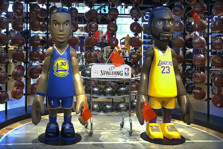 Statues of NBA players Stephen Curry of the Golden State Warriors, left, and Lebron James of the Los Angeles Lakers hold Chinese flags in the entrance of an NBA merchandise store in Beijing, Tuesday, Oct. 8, 2019. Chinese state broadcaster CCTV announced Tuesday it will no longer air two NBA preseason games set to be played in the country. (AP Photo/Mark Schiefelbein) Photo: Mark Schiefelbein / Associated Press