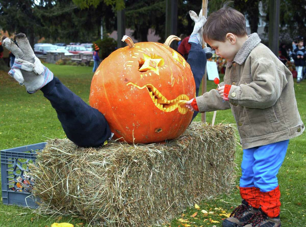 SUB 20041023 KD 013 Nicholas Sorrentino, 3, tugs the tongue of frightening pumpkin at Stratford's Great Annual Pumpkin Festival Saturday. Keelin Daly/ For the Register