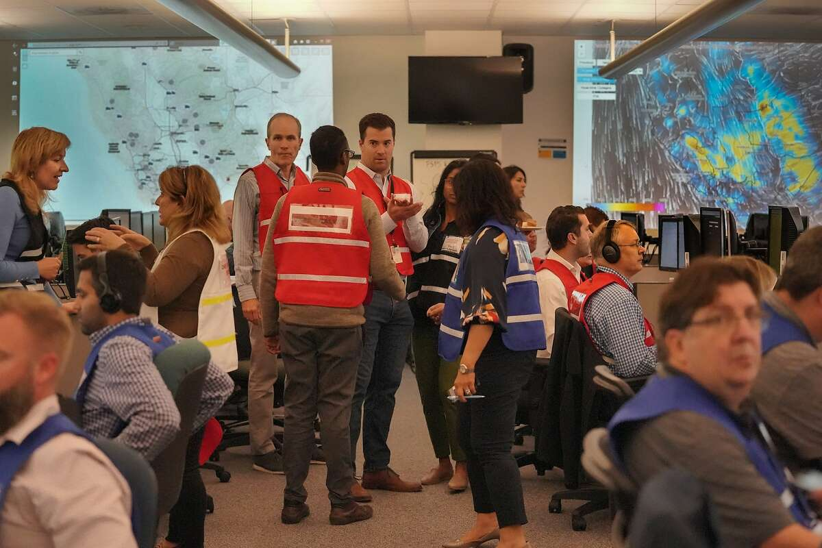 PG&E employees gather at their emergency operations center where public safety shutoff was confirmed for nearly 800,000 customers in Calif. on Tuesday, Oct. 8, 2019 in San Francisco, Calif.