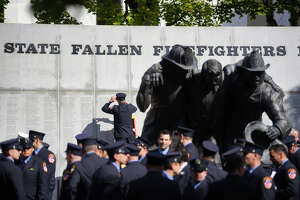 Firefighters gather at the wall listing the names of firefighters who have died in the line of duty following a ceremony on Tuesday, Oct. 8, 2019, in Albany, N.Y.   (Paul Buckowski/Times Union)