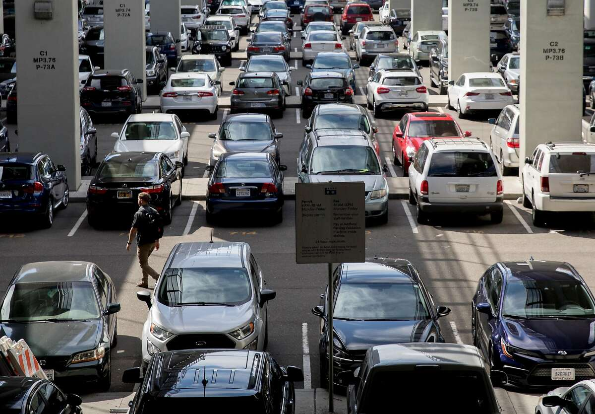 A man walks through rows of parked cars in the lots at Rockridge BART Station in Oakland, Calif. Tuesday, Oct. 8, 2019. BART is considering increasing its parking fees.