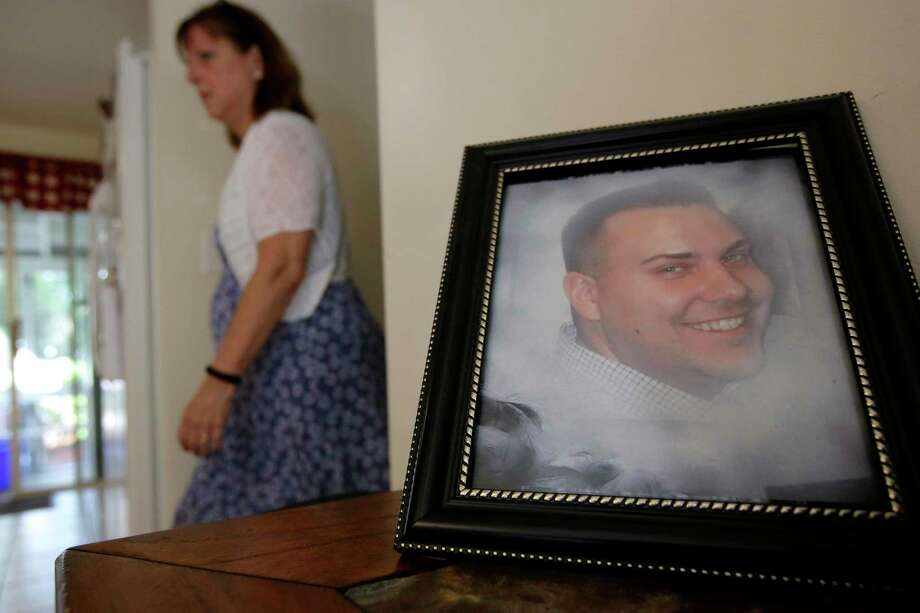 FILE - In this Tuesday, June 19, 2018 file photo Cheryl Juaire walks past a photo of her son, Corey Merrill, at her home in Marlborough, Mass. Victims of opioid addiction weren't in the room when big decisions were hammered out in OxyContin maker Purdue Pharma's proposal to settle claims over its role in the U.S. opioid crisis. Cheryl Juaire lost her 23-year-old son to a heroin overdose after he became addicted to prescription painkillers. (AP Photo/Steven Senne, File) Photo: Steven Senne / Associated Press / Copyright 2018 The Associated Press. All rights reserved.