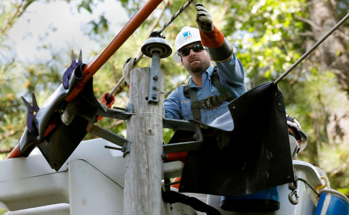 PG&E's Taylor Flosi and Rob Thomas, (back) repair a power line that had come loose from an insulator which was discovered during patrols in the area as PG&E performed a public safety power shutoff drill around Foresthill, Ca. on Thurs. August 8, 2019. Helicopters and trucks, are used in a trial run for how it will inspect power lines before turning them on after a shut down.