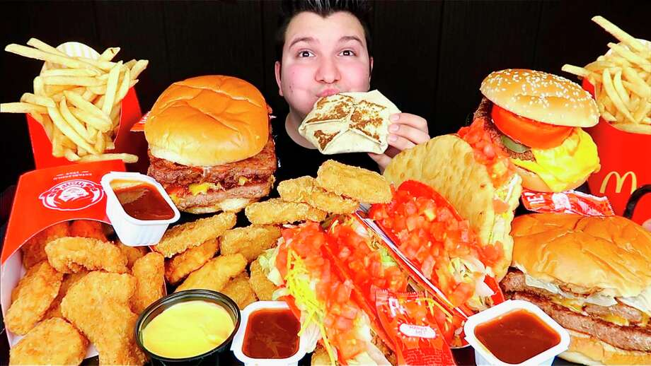 This image taken from video and released by Nikocado Avocado shows him surrounded by items from fast-food chains Wendy's and Taco Bell. Nikocado Avocado, whose real name is Nicholas Perry, 27, has three mukbang channels with 1.71 million subscribers on the largest. He's a classically trained violinist who gave up that career struggle for mukbang in 2016. Photo: Nikocado Avocado, HONS / Associated Press / Nikocado Avocado