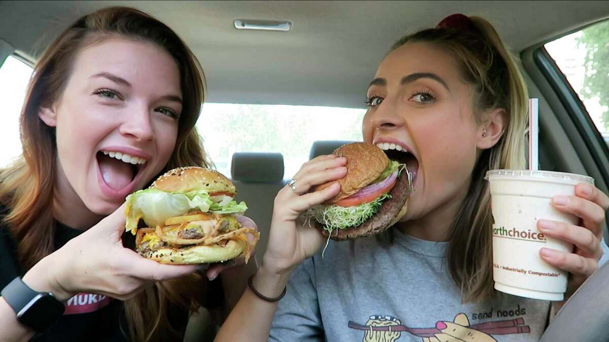 This image made from video released by Brittany Marsicek shows dancer-actor Marsicek, 28, left, and actor Chantal Plamondon, 27, during the filming of their Mukbang Monday channel. The two focus on vegan food, reviewing the latest fast-food offerings, and often film in their cars as they chat about auditions and day jobs while munching from fast-food containers.