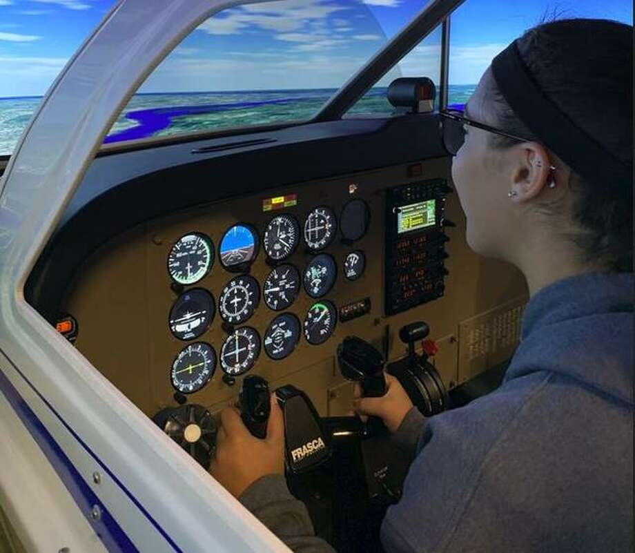 Alton High School sophomore McKenna Tosh uses a flight simulator during Girls in Aviation Day, Oct. 4, at St. Louis Downtown Airport in Cahokia. About 120 girls attended the second annual event.