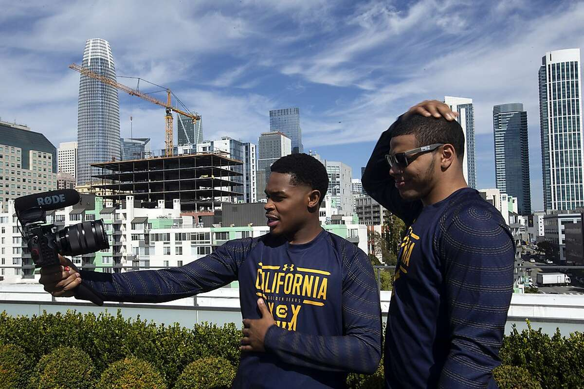California's Paris Austin, left, and Matt Bradley make a video on the roof of the Pac-12 headquarters during the Pac-12 NCAA college basketball media da, in San Francisco, Tuesday, Oct. 8, 2019. (AP Photo/D. Ross Cameron)